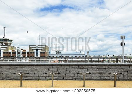 OOSTENDE BELGIUM - JUNE 22 2016: Oostende pier with a bicycle parking lot a stone wall with buildings and seagulls in the background in a cloudy day. Oostende Belgium.