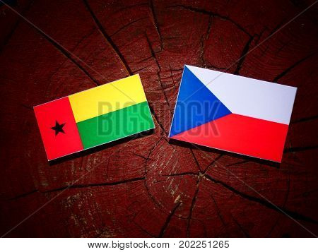 Guinea Bissau Flag With Czech Flag On A Tree Stump Isolated