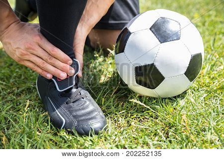 Close-up Of Male Soccer Player Suffering From Ankle Injury On Field