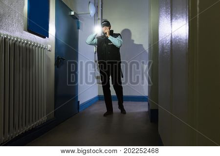 Male Security Guard With Flashlight Standing In Corridor Of The Building