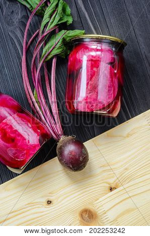 Canned homemade beetroot in clear glass jars with fresh organic beetroots on a black wooden background top view. Copy space for your text message top vew