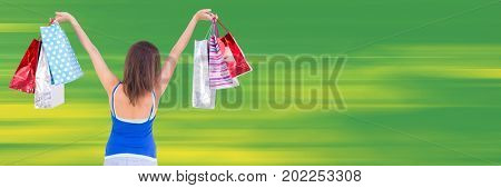 Digital composite of Back of shopper with bags in air against blurry green background