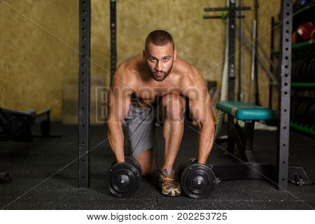A full-length photo of a brutal and sexy fitness model man execute exercise with dumbbells on a gym background. A bodybuilder with a perfect body working out in a fitness gym. Sports concept.