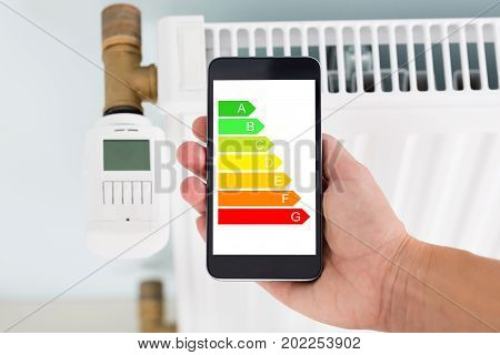 Closeup of man's hand using energy label on mobile phone against radiator at home