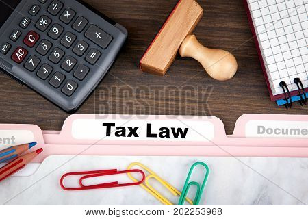 tax law concept. Folder Register on a dark wooden desk.