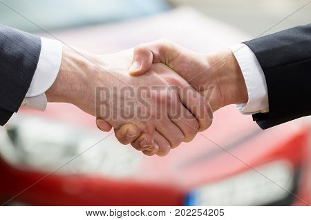 Cropped closeup of salesman shaking hands with client after selling car at dealership