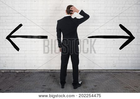 Full length rear view of confused businessman looking at opposite arrow signs on wall
