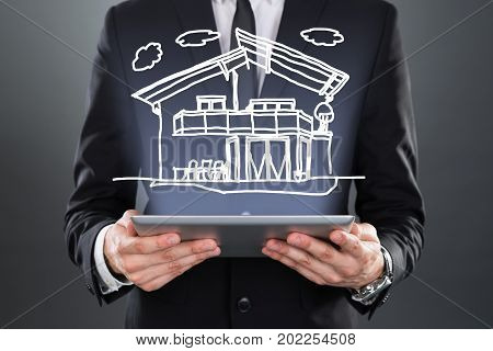 Midsection of businessman showing model home over digital tablet against gray background