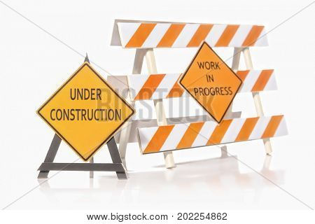 Construction warning barriers with Work in Progress and Under Construction signs over white background