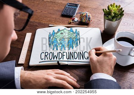 Man Drawing Crowdfunding Concept In Notepad At Desk