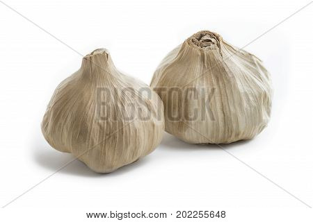 pair of whole bulb of home fermented Black Garlic. Latest wonder food rich in antioxidants vitamins and minerals. On a isolated white background