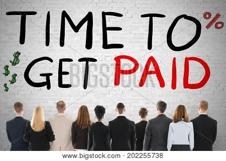 Group Of Diverse People Looking At Time To Get Paid Words