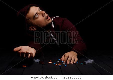 A portrait of a scared young addict man with a lot of narcotic pills and syringes full of bad red liquid on a saturated black background. An overdose of drugs. Fear, depression and narcotic concept.