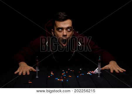 An addict sitting at the table with colorful pills and syringes on a saturated black background. An overdose of drugs. Addiction, fear, abuse and depression concept. Copy space.