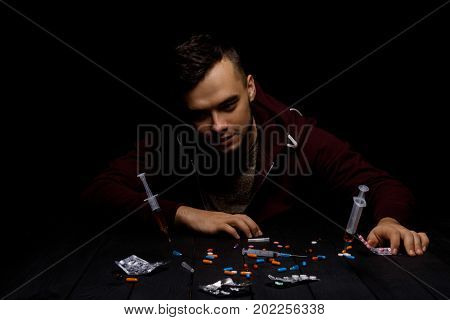 An addict male clings to his head with his own hands sitting at the table on a black background. A hopeless drug addict is going through addiction crisis. A lot of colorful narcotics on a desk.
