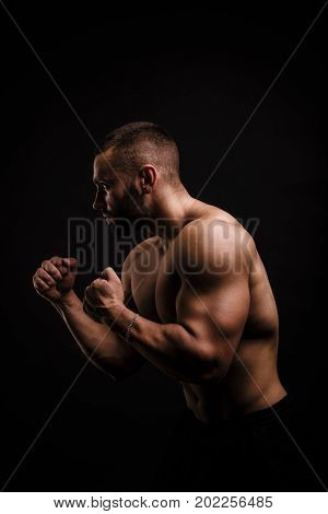 A brutal, fit adult man in comfortable sports shorts doing hard excersises on the black background. A strong male bodybuilder working out. Sexy macho model building muscles. poster