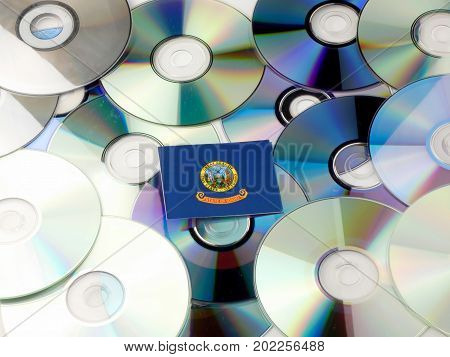Idaho Flag On Top Of Cd And Dvd Pile Isolated On White
