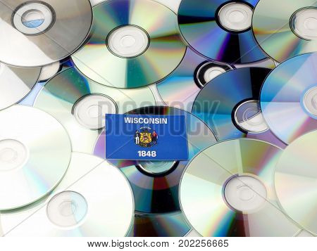 Wisconsin Flag On Top Of Cd And Dvd Pile Isolated On White