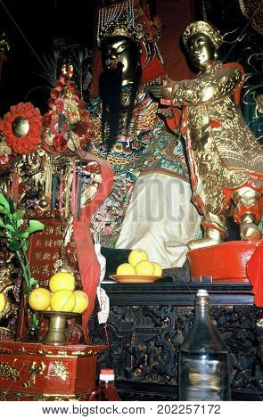 SINGAPORE / CIRCA 1990: Religious sculptures stand on an altar inside the historic Siong Lim Temple, also known as Lian Shan Shuang Lin Monastery, in Singapore.