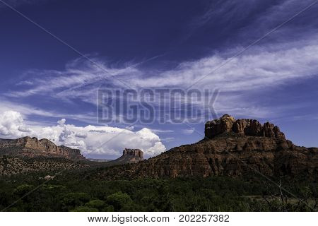 Colorful rock formations and a distant thunderstorm create a striking vista near Sedona, Arizona