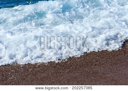Sea foam. The wave breaks about the shore. Sea pebbles