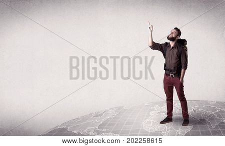Handsome young man with a backpack on his back standing on a world map