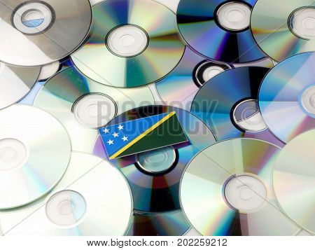 Solomon Islands Flag On Top Of Cd And Dvd Pile Isolated On White