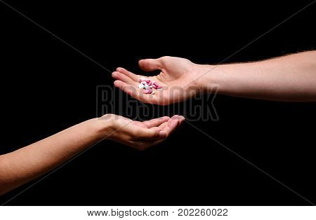 Close-up picture of a man giving different meds to a woman. Hands holding white and pink painkillers, antibiotics, drugs, vitamins or aspirin in round tablets on the black background.