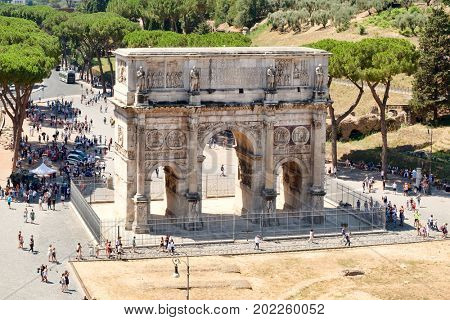 The triumphal Arch of Constantine next to the ruins of the Colosseum in Rome