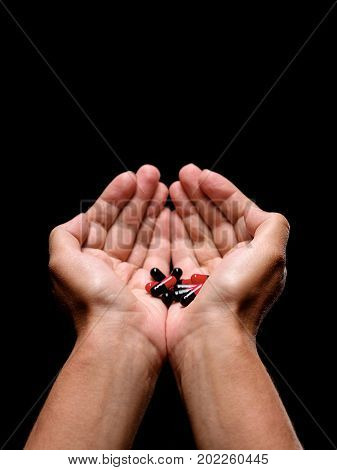 Close-up of opened man's palms holding red and black capsules with drugs on the black background. Hands showing healthy vitamins in capsules. Healthy lifestyle and healthcare concept. Copy space.