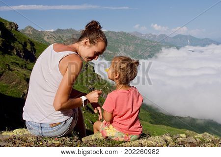 Young woman with little cute daughter sitting on top of the mountain. Family higher than clouds admiring beautiful view.