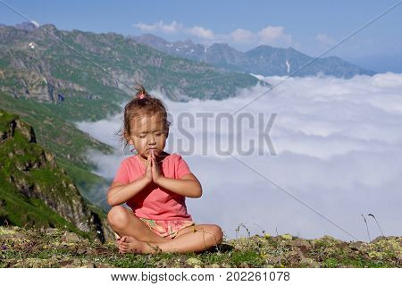 Little cute girl meditating on top of mountain. Portrait of child meditating in lotus pose higher than clouds.