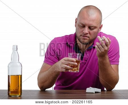 A depressed man in a crimson T-shirt is holding a transparent glass full of whiskey and a cigarette, isolated on a white background. A sad boozed male with an alcoholic drink on a wooden table.