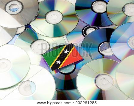 Saint Kitts And Nevis Flag On Top Of Cd And Dvd Pile Isolated On White