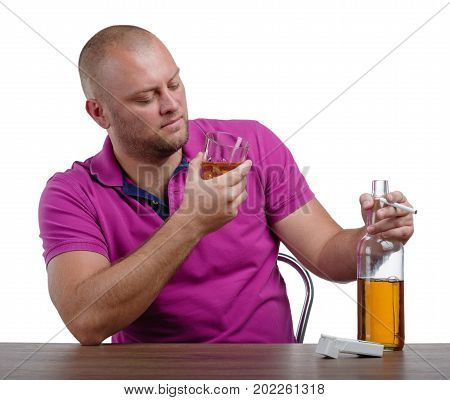 A close-up of a man looking at glass full of whiskey, a big bottle, and a cigarette, isolated on a white background. A boozed male with an alcoholic drink and pack of cigarettes on a wooden table.