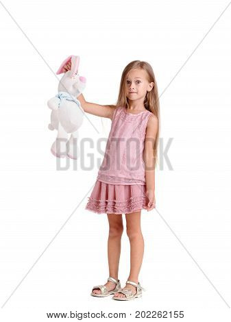 A portrait of a beautiful little girl with a big soft toy, isolated on a white background. A cute and shocked baby girl with long blonde hair is holding for ears a soft toy rabbit. Copy space.