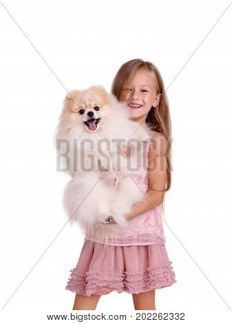 A portrait of a charming and happy little girl with a fluffy puppy, isolated on a white background. A cute baby girl with long hair in a pink dress is hugging a small dog. Copy space.