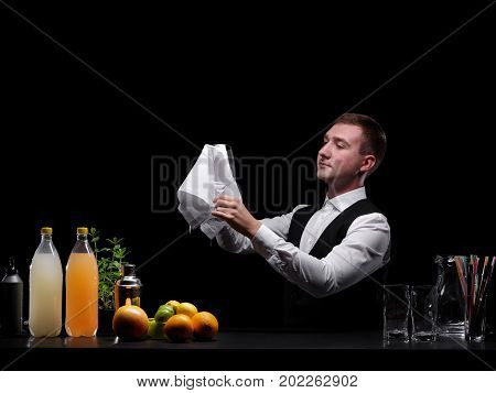 Confident, beautiful barman cleaning a shaker or a glass on the black background. Fruits, juices for cocktails and glasses on a table and a club bartender in black and white classic suit. Copy space.