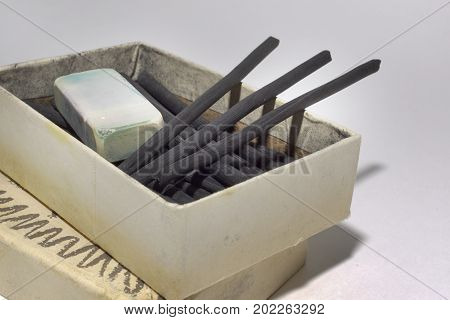 Natural Charcoal Sticks And Dirty Eraser In An Old Cardboard Box. Vintage Art Materials For Draw. Cl