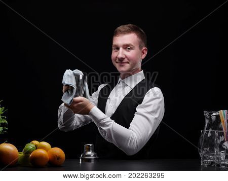 Confident, smiling barman cleaning a shaker or a glass on the black background. Fruit ingredients and glasses on a bar counter and a club bartender in black and white classic suit. Copy space.