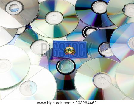 Vermont Flag On Top Of Cd And Dvd Pile Isolated On White
