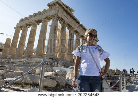 Blond woman exploring in acropolis, parthenon in view