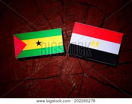 Sao Tome And Principe Flag With Egyptian Flag On A Tree Stump Isolated