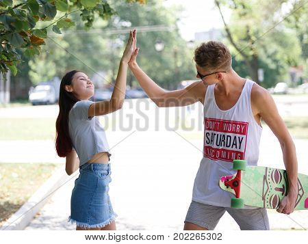 A beautiful young fall-in-love couple on a blurred natural background. A happy teenage boy and a pretty girl are giving each other five outdoors. Love, youth, happiness, romance concept. Copy space.