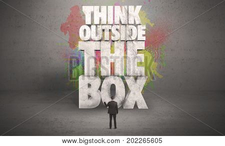 Colorful wall with illustrated quote saying think outside the box for a small businessman standing in grey urban space concept