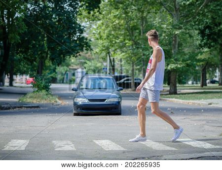 Awkward, careful young guy crossing a street in front of a moving car on the blurred street background. An irresponsible casual male student running down the street with cars. Copy space.