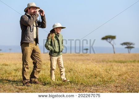 Family of father and child on African safari vacation enjoying bush view