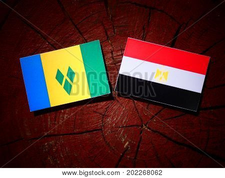 Saint Vincent And The Grenadines Flag With Egyptian Flag On A Tree Stump Isolated