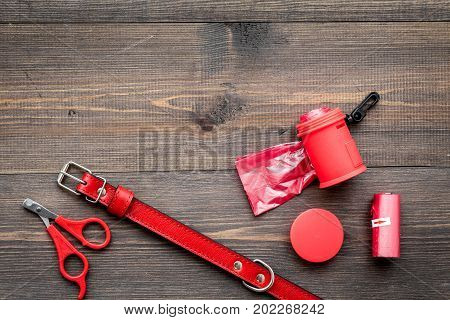 red grooming equipment with collar for care and training pet on wooden desk background top view mock up