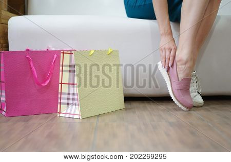 A woman sitting on a sofa and choosing a perfect pair of shoes on a shop background. A female holding trendy pink boots in a luxury boutique. Fashionable girl with colorful bags shopping in a store.